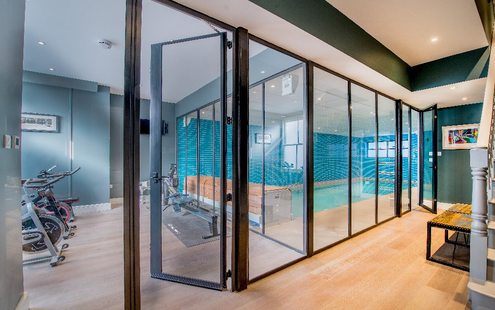 Gymnasium and pool in London basement divided in style