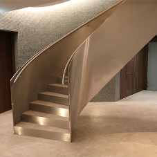Contemporary, curved stainless steel staircase for high end residential spa
