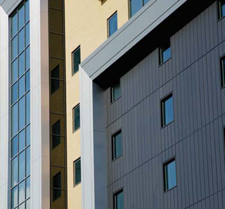 The Optima TFC cassette rainscreen system features panels in an antique copper finish and Optima IPC zinc planks